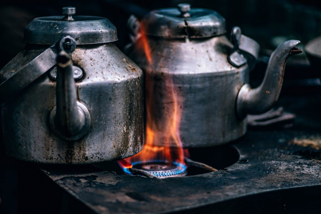 Charred metal kettles on open fire stove top