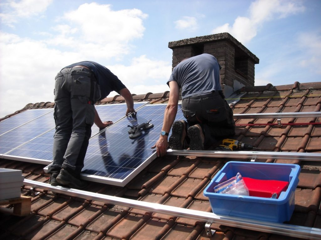 Image of men installing solar panels on a roof.
