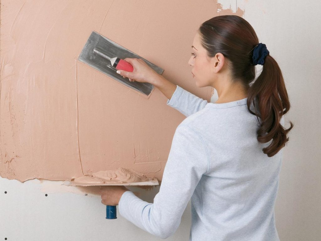lady plastering a wall