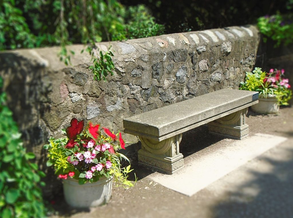 image of a stone wall with a stone bench in front of it