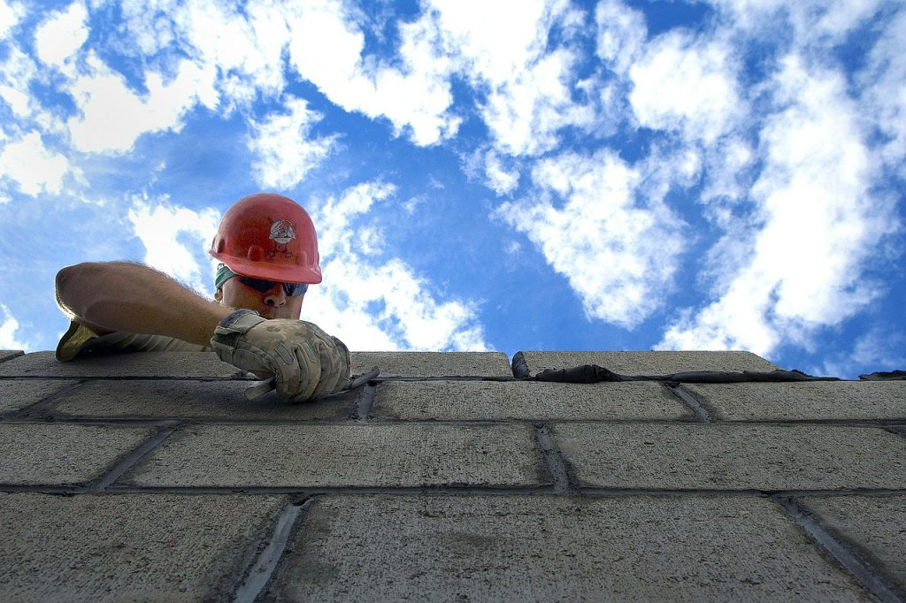 image of a man building a brick wall